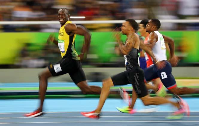 Ο Usain Bolt της Τζαμάικα κοιτάει τον Andre De Grasse του Καναδά καθώς αγωνίζονται στους ημιτελικούς των 100 μέτρων στους Ολυμπιακούς Αγώνες του Ρίο, στις 14 Αυγούστου 2016. REUTERS/Kai Pfaffenbach