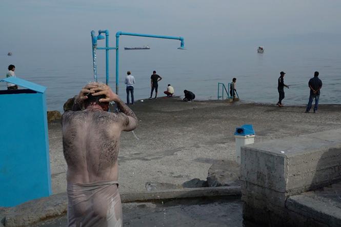 Chien-Chi Chang. Πρόσφυγες περνούν την ώρα τους ψαρεύοντας και κάνοντας μπάνιο, περιμένοντας να γυρίσουν στο καταυλισμό, Λέσβος 2016