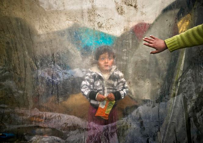 Ένα παιδάκι πίσω από ένα πλαστικό κάλυμμα στην Ειδομένη, 15 Μαρτίου 2016. Vadim Ghirda—AP