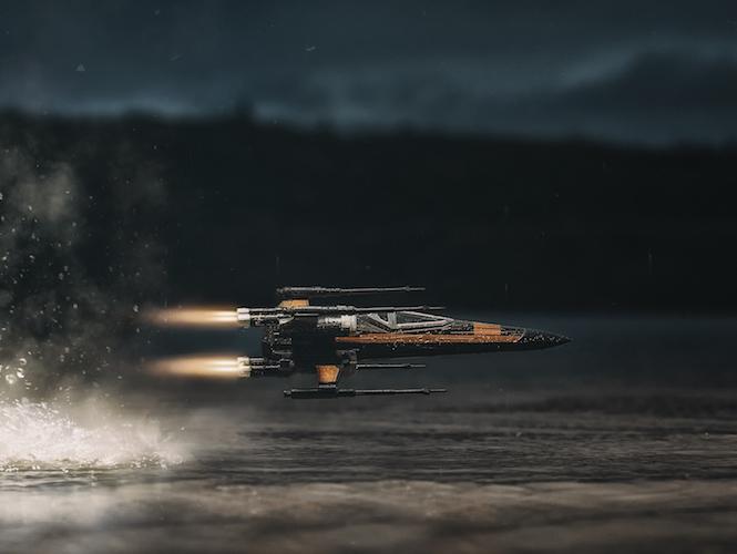 Φωτογράφιση ενός X-Wing Starfighter παιχνιδιού να πετάει πάνω από νερό